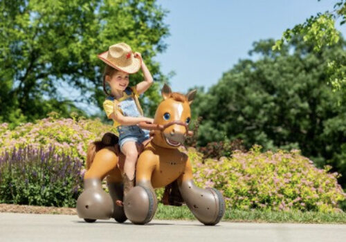 photo of a young child riding a KidTrax Rideamals Scout outside