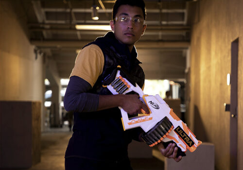photo of a man holding a nerf ultra toy gun in a hallway