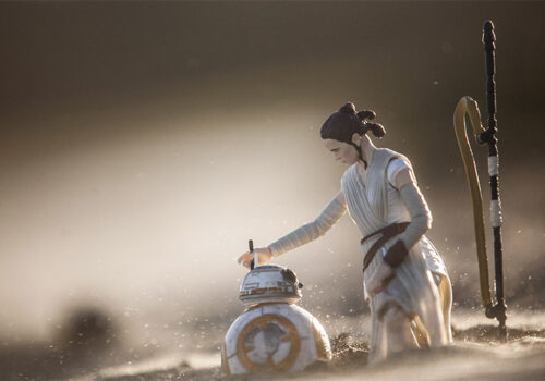 photo of star wars toys in sand with a blurry background