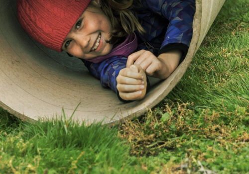 photo of a young child playing in a large tube rolling on the grass