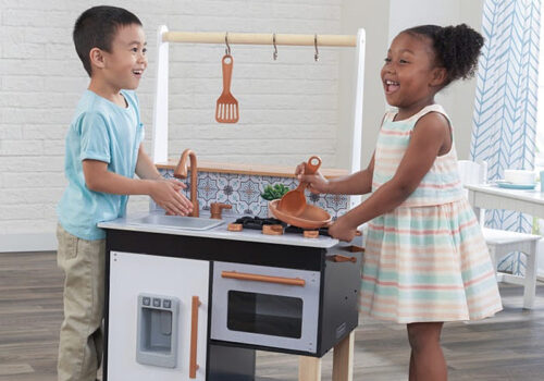 photo of two children playing with a Kid Kraft toy kitchen set