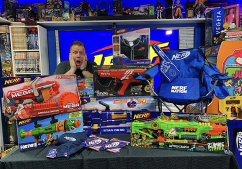 photo of a man gasping with two hands on his face behind a table full of nerf merchandise