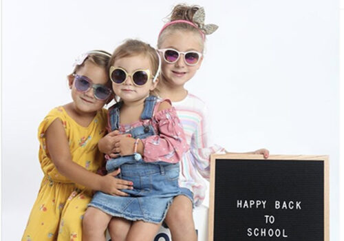 photo of three young children wearing sunglasses and oshkosh clothing with a happy back to school sign