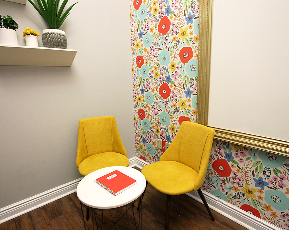 photo of two chairs and a table sitting in the corner of a room with flower wallpaper and a shelf