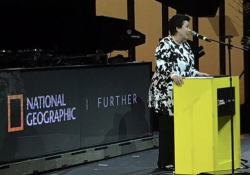 photo of a woman speaking behind a podium in front of a national geographic further sign